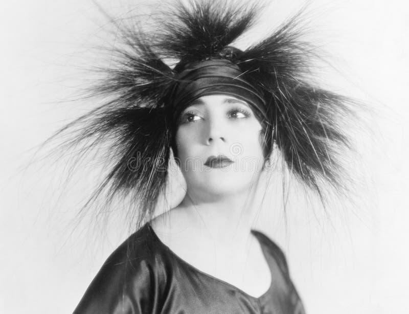 Jeune femme élégante semblant sereine dans un chapeau de plume (toutes les personnes représentées ne sont pas plus long vivantes  image stock