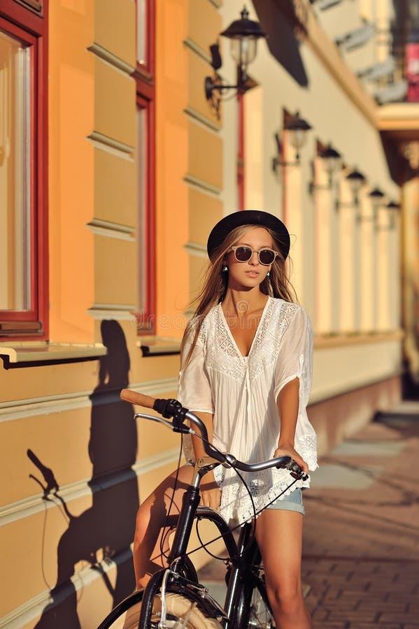 Jeune femme élégante sur une rétro bicyclette Verticale extérieure de mode images stock