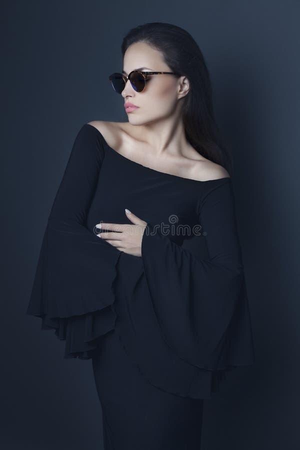 Jeune femme élégante utilisant la robe et les lunettes de soleil noires photographie stock libre de droits