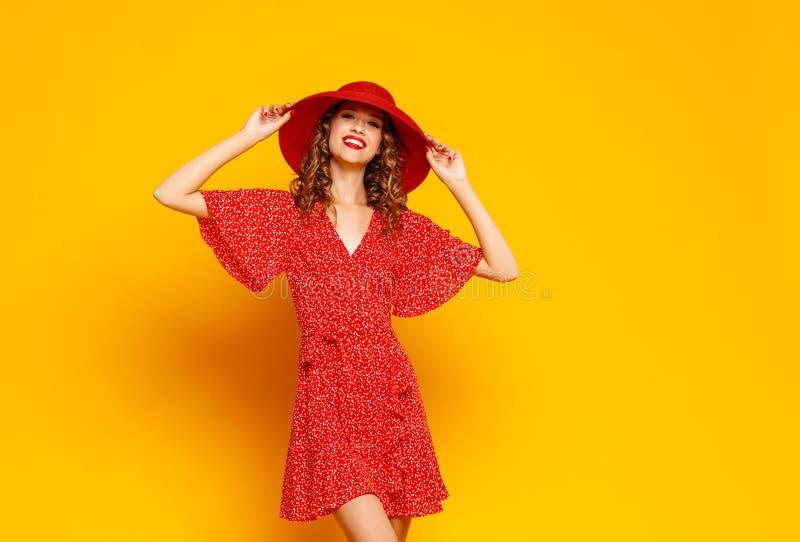 Jeune femme émotive heureuse de concept dans la robe rouge et le chapeau d'été sautant sur le fond jaune photographie stock