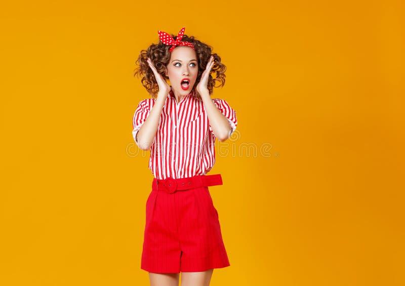 Jeune femme émotive heureuse de concept dans sauter rouge sur le fond jaune photographie stock libre de droits