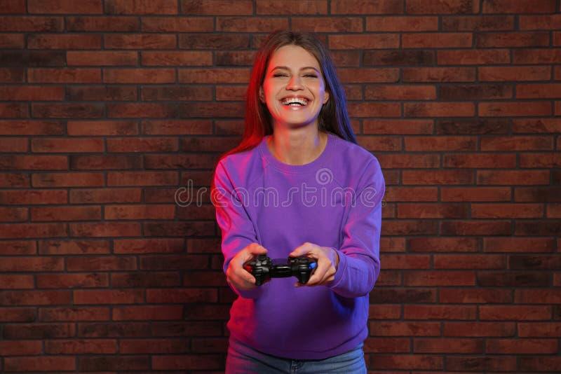 Jeune femme émotive jouant des jeux vidéo avec le contrôleur près du mur photo stock