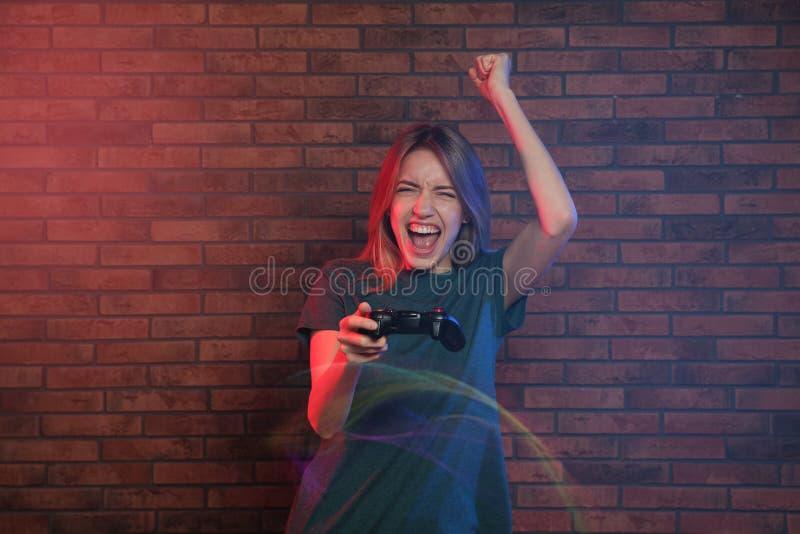 Jeune femme émotive jouant des jeux vidéo avec le contrôleur près du mur photo libre de droits