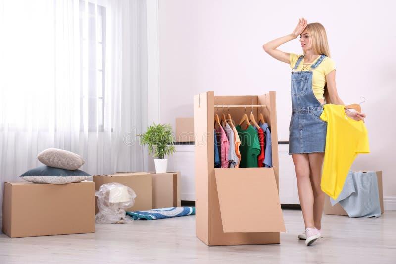 Jeune femme émotive près de boîte de garde-robe images stock