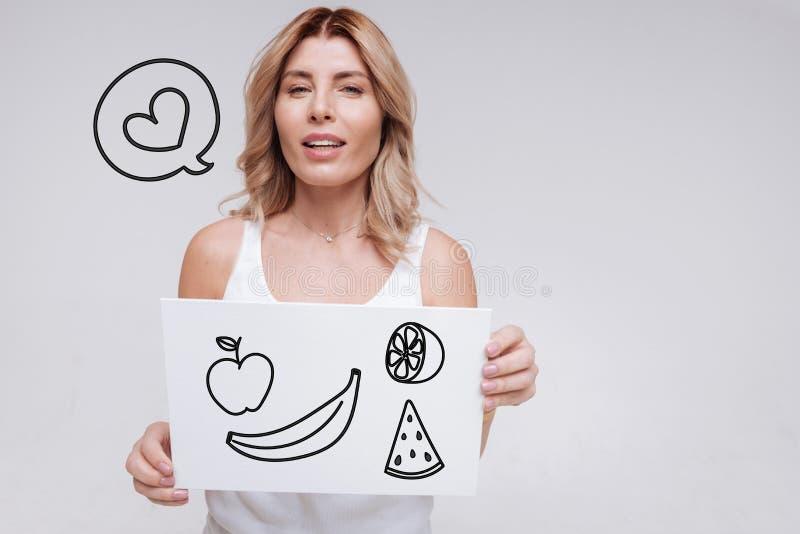Jeune femme émotive souriant tout en pensant au fruit frais de achat photo libre de droits