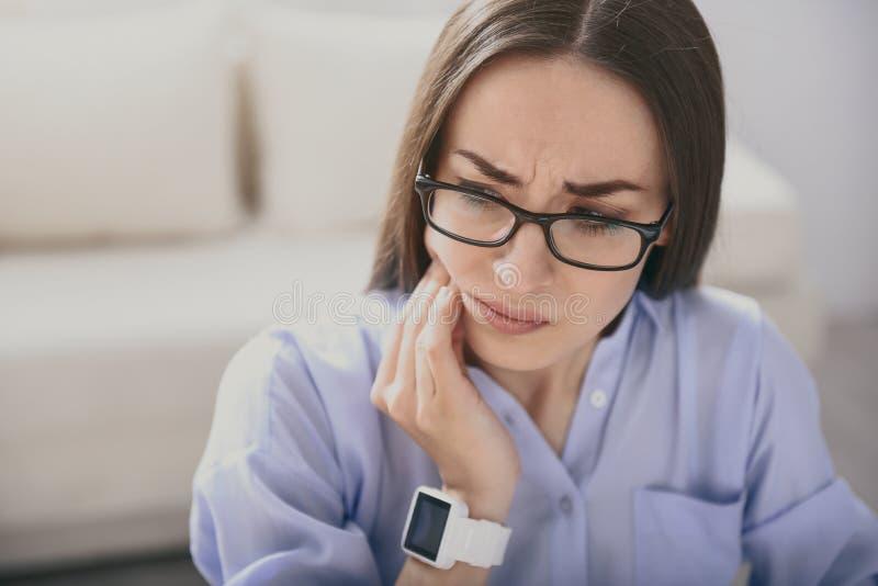 Jeune femme épuisée ayant le mal de dents image libre de droits