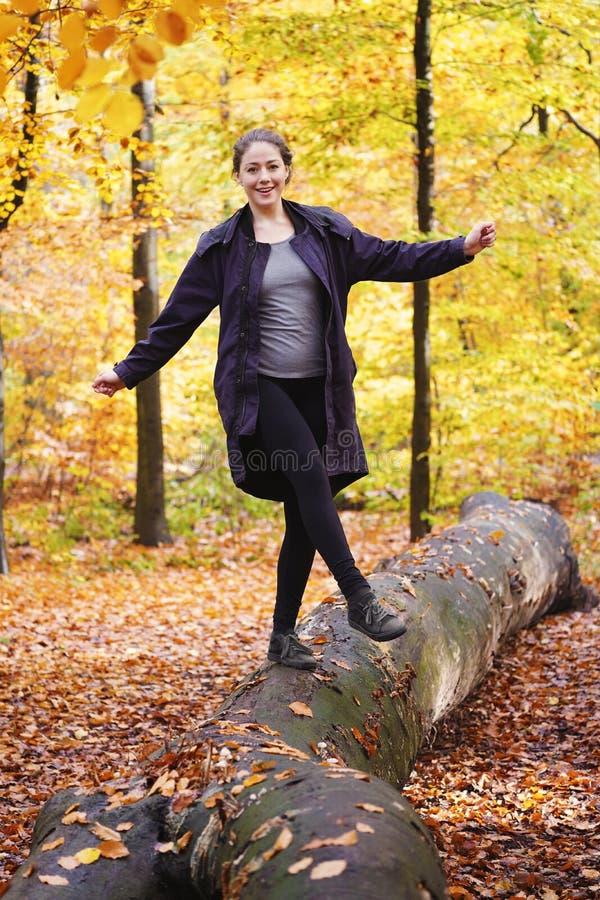 Jeune femme équilibrant sur le tronc d'arbre dans la forêt dans la chute photographie stock