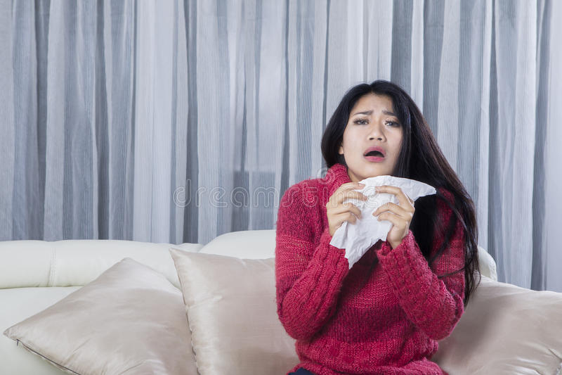 Jeune femme éternuant à la maison images libres de droits