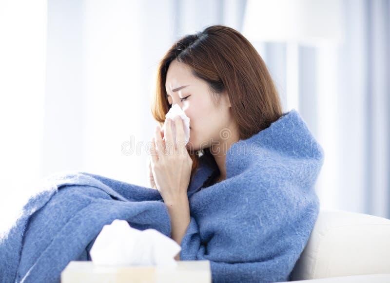 Jeune femme éternuant et soufflant son nez photos libres de droits