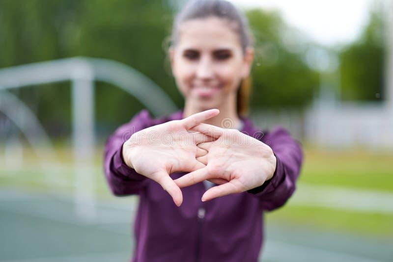 Jeune femme étirant des bras à l'extérieur Exercice faisant femelle d'échauffement de forme physique au parc, foyer sur des mains images stock