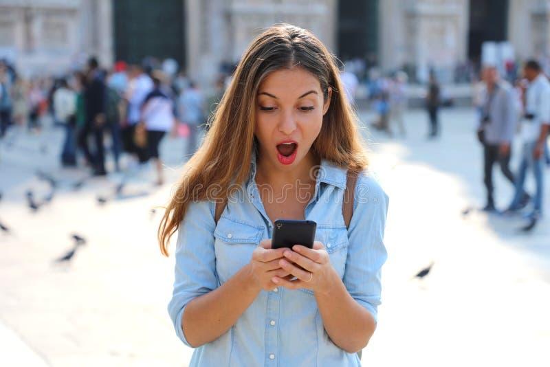 Jeune femme étonnée à l'aide du téléphone intelligent dehors Fermez-vous vers le haut du portr images stock