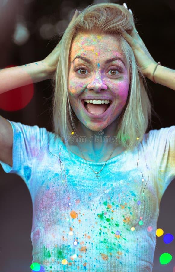 Jeune femme étonnée avec la peinture de Holi sur son visage posant avec la Co images libres de droits