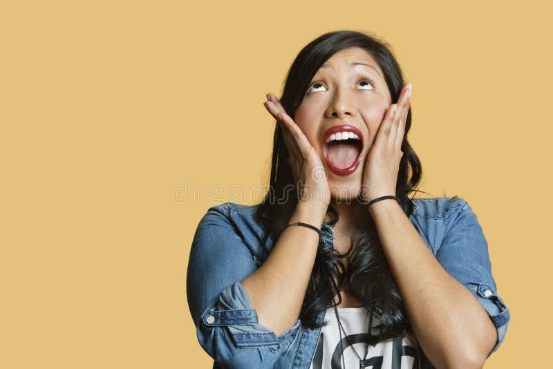 Jeune femme étonnée avec la tête dans des mains recherchant au-dessus du fond coloré photos stock