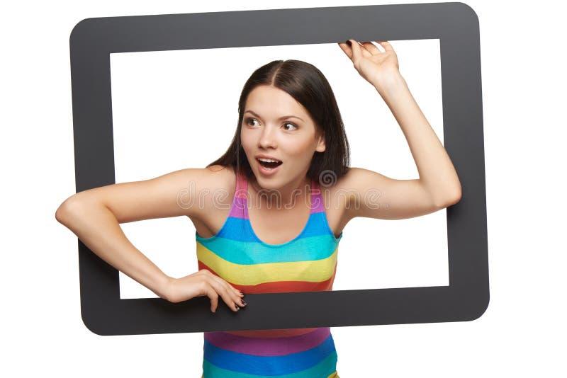 Jeune femme étonnée brouillant hors du cadre de comprimé photos stock