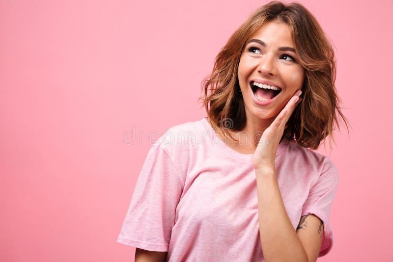 Jeune femme étonnée d'isolement au-dessus du fond rose photos stock