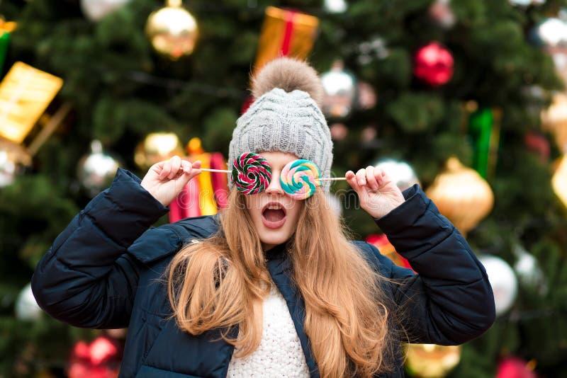 Jeune femme étonnée dans le chapeau tricoté tenant des bonbons à Noël à photographie stock