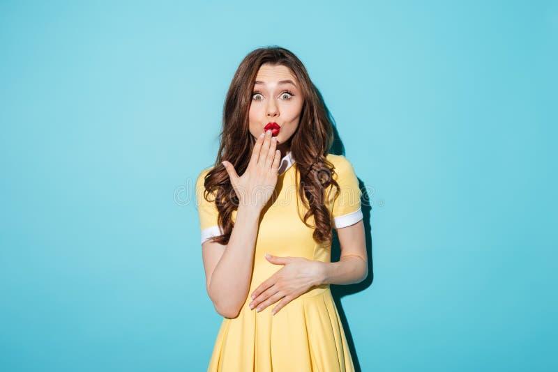 Jeune femme étonnée de brune dans la robe jaune images stock