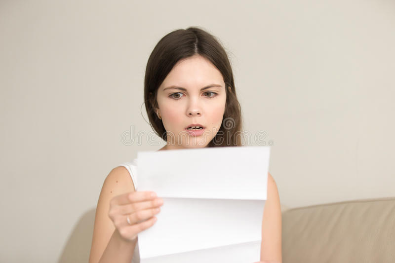 Jeune femme étonnée lisant la lettre inattendue image libre de droits