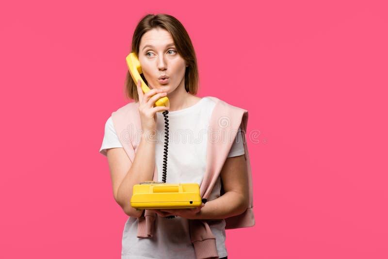 jeune femme étonnée parlant par le téléphone rotatoire d'isolement photo libre de droits