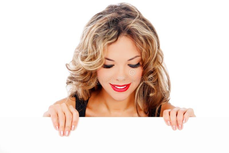 Jeune femme étonnée regardant le panneau-réclame blanc photo libre de droits