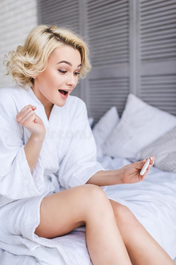 jeune femme étonnée tenant l'essai de grossesse positif images stock