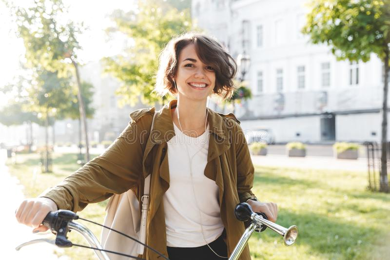 Jeune femme étonnante mignonne marchant dehors en parc avec la belle journée de printemps de bicyclette photographie stock libre de droits