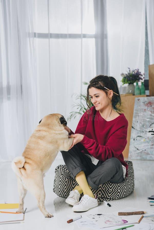 Jeune femme étreignant le chien mignon sur le plancher photo libre de droits