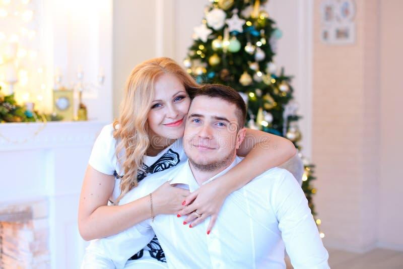 Jeune femme étreignant le mari près de l'arbre de Noël images stock