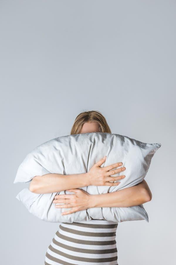Jeune femme étreignant un oreiller gris photo stock
