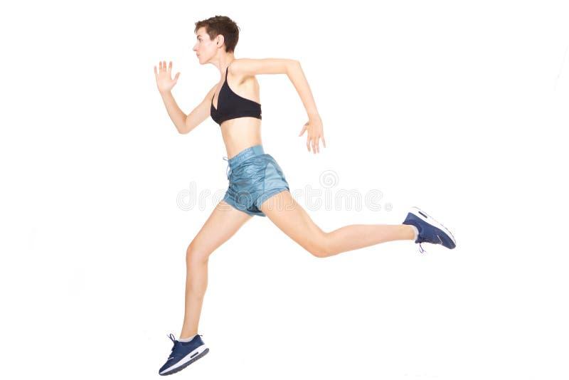 Jeune femme active intégrale sautant sur le fond blanc d'isolement photographie stock