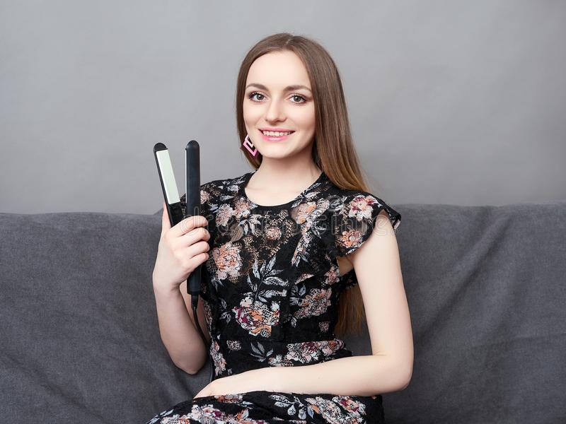 Jeune femme adorable heureuse dans la longue robe sur le sofa gris tenant le styler de cheveux à la maison contre le mur gris photos stock