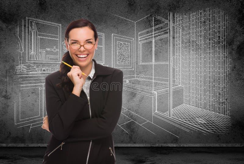 Jeune femme adulte avec le crayon devant le dessin d'étude de salle de bains sur le mur images stock