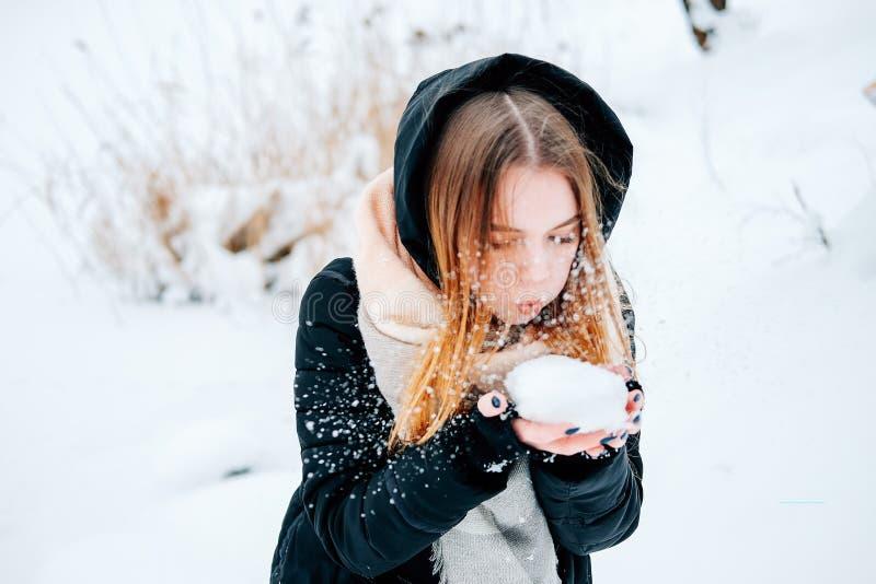 Jeune femme adulte blonde attirante ayant l'amusement avec la première neige photo stock