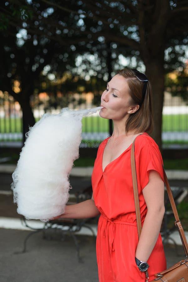 Jeune femme adulte dans la robe rouge mangeant la sucrerie de coton au parc photographie stock