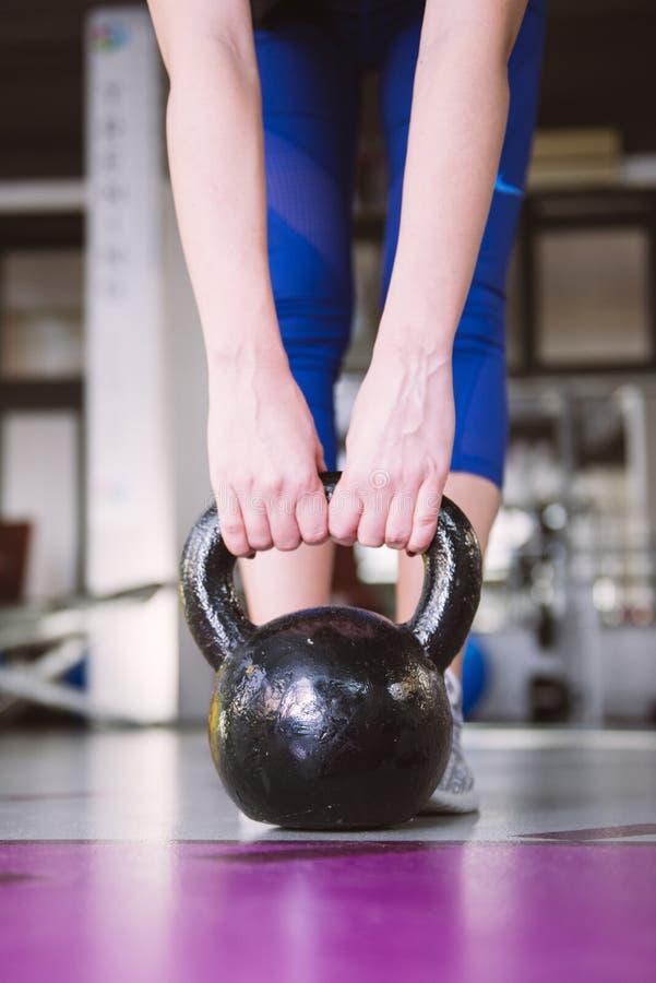 Jeune femme adulte de forme physique faisant l'exercice d'oscillation avec un kettlebell photographie stock libre de droits