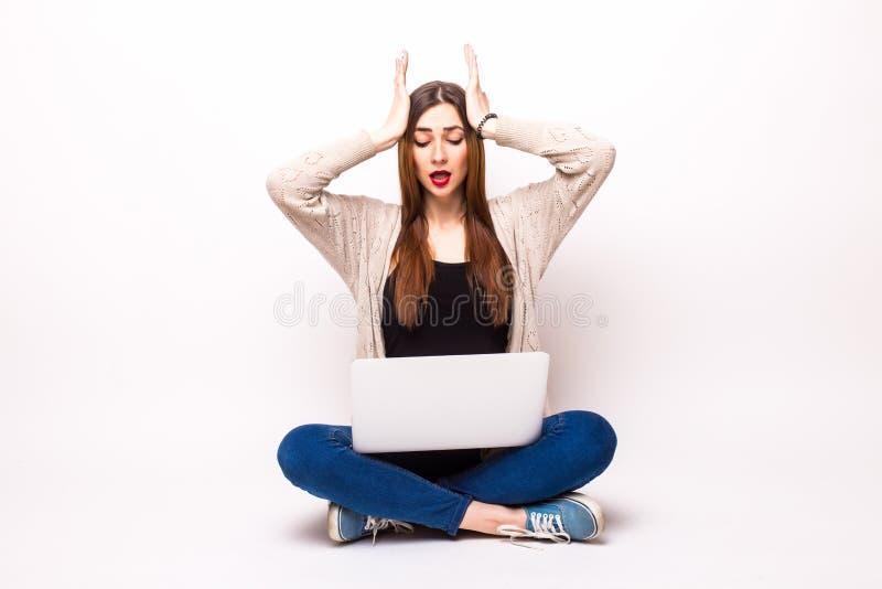 jeune femme adulte en passant habillée regardant fixement son ordinateur portable dans la surprise images stock