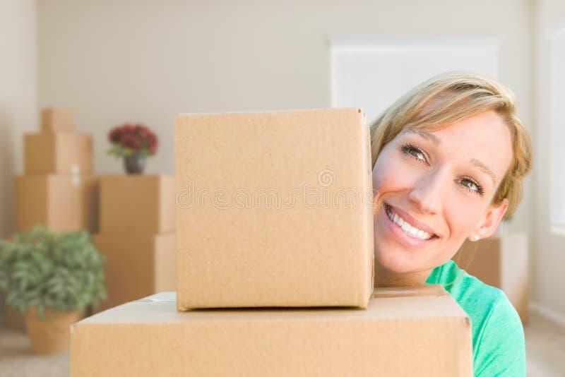 Jeune femme adulte heureuse tenant les boîtes mobiles dans la chambre vide dans A photographie stock