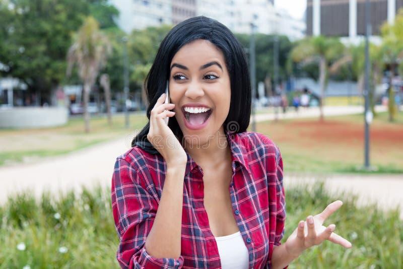 Jeune femme adulte latino-américaine indigène riant du téléphone photographie stock