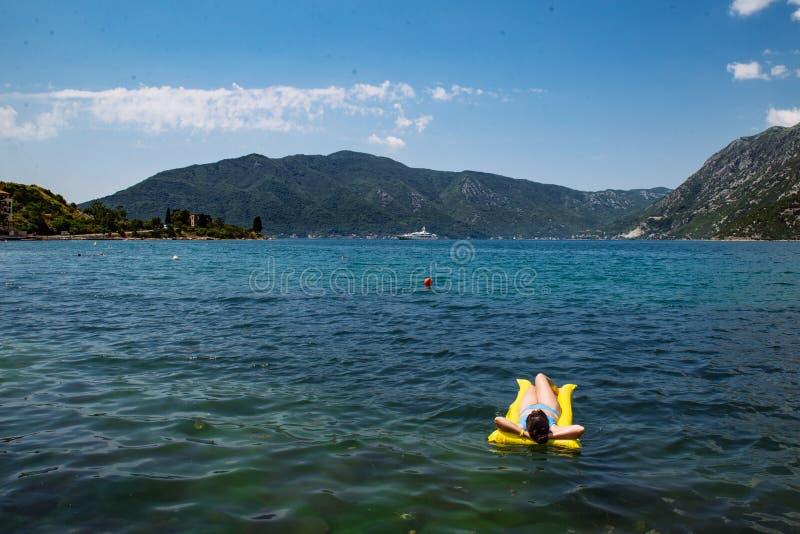Jeune femme adulte sur le matelas jaune en eau de mer bleue photos libres de droits