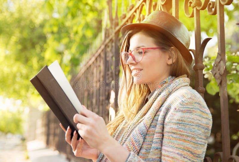 Jeune femme affichant un livre à l'extérieur photographie stock libre de droits