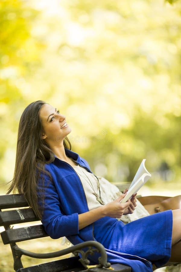 Jeune femme affichant un livre en stationnement image libre de droits