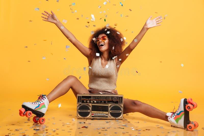 Jeune femme africaine avec du charme dans les rétros scates thr d'usage et de rouleau photo stock