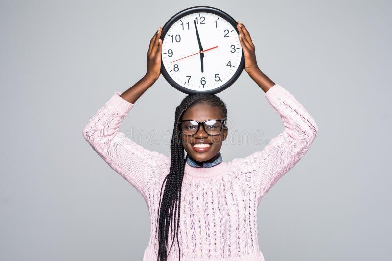 Jeune femme africaine avec la grande horloge ronde d'isolement au-dessus du fond gris photos libres de droits