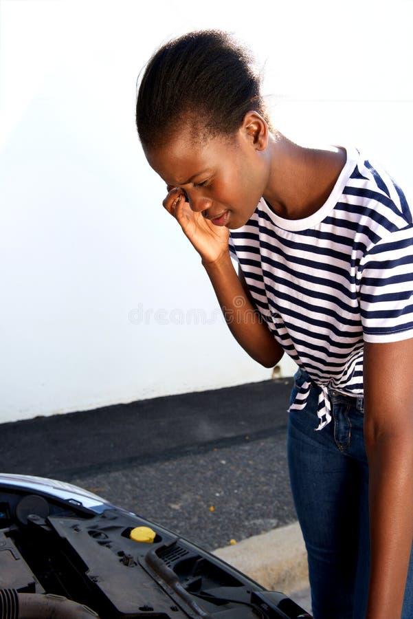 Jeune femme africaine ayant des ennuis avec sa voiture cassée réclamant l'aide au téléphone portable photos stock