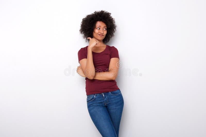Jeune femme africaine bouleversée se dirigeant vers l'arrière avec son pouce sur le fond blanc photos stock