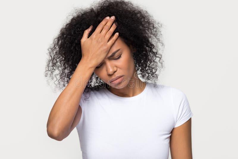 Jeune femme africaine bouleversée touchant le mal de tête de sentiment de front photo libre de droits