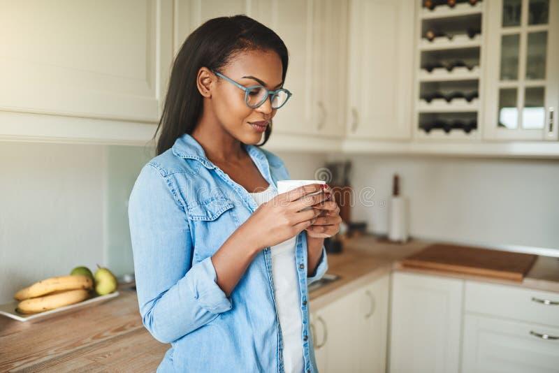 Jeune femme africaine buvant une tasse de café à la maison image libre de droits