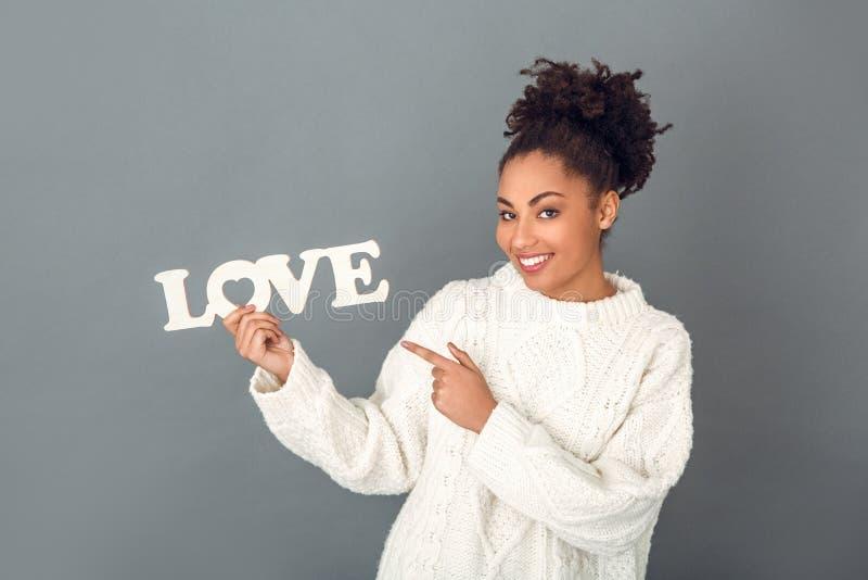 Jeune femme africaine d'isolement sur la valentine grise de concept d'hiver de studio de mur images stock