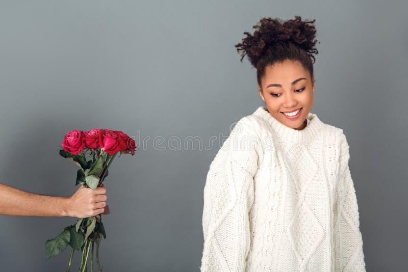 Jeune femme africaine d'isolement sur le concept gris d'hiver de studio de mur timide image libre de droits