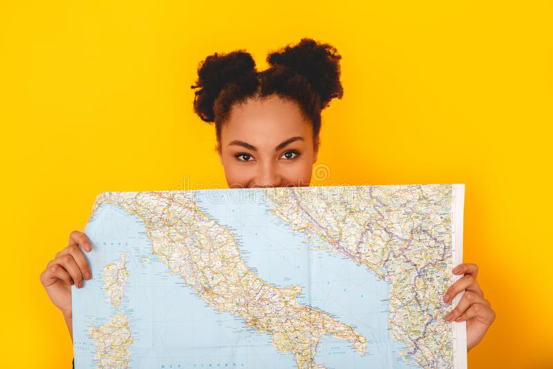 Jeune femme africaine d'isolement sur le voyageur de l'adolescence de style de studio jaune de mur se cachant derrière la carte photos stock